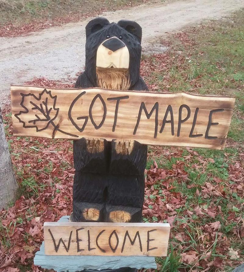 """wooden bear with a sign saying """"Got Maple"""""""